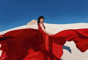 Девушка в красном платье на фоне песка