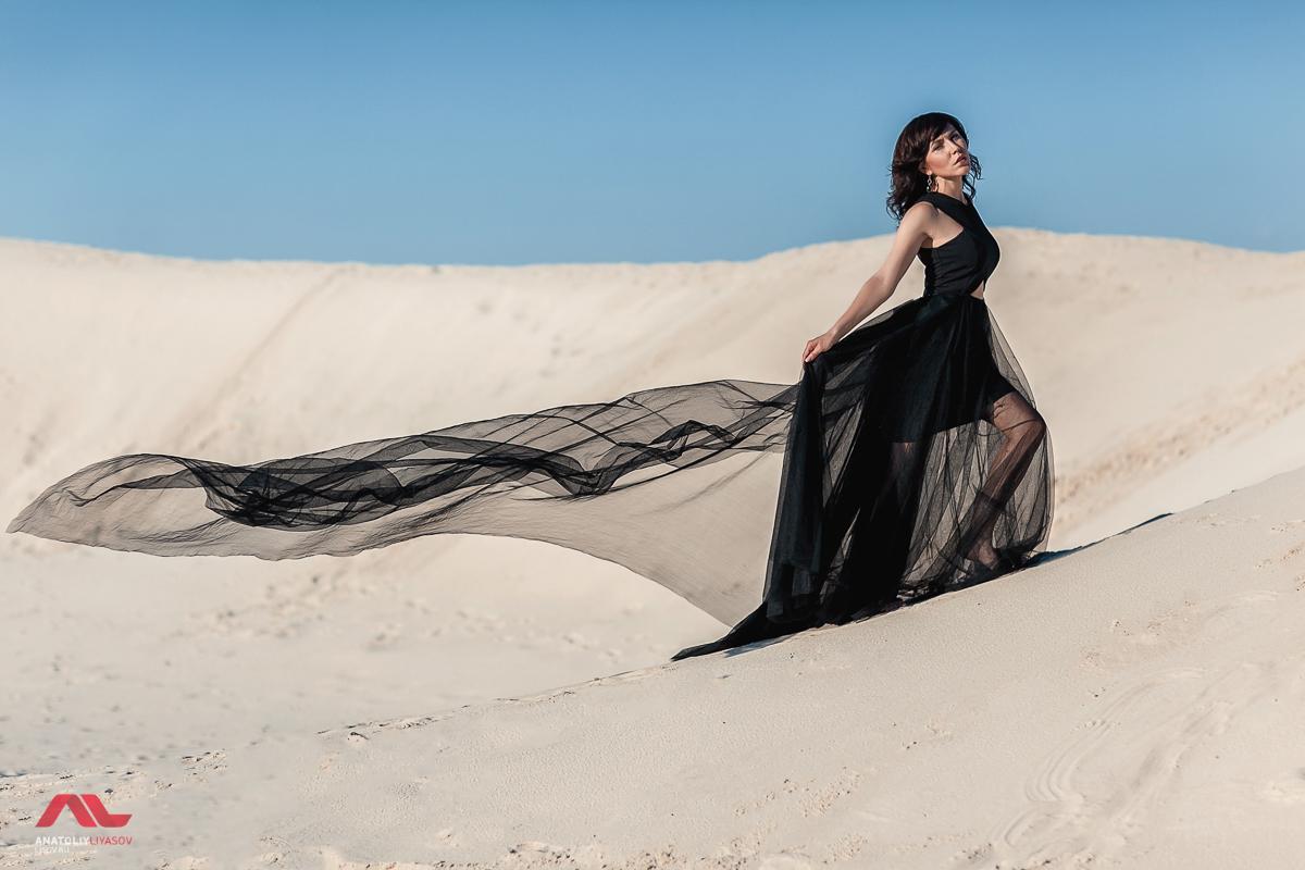 Девушка в черном платье на фоне песка