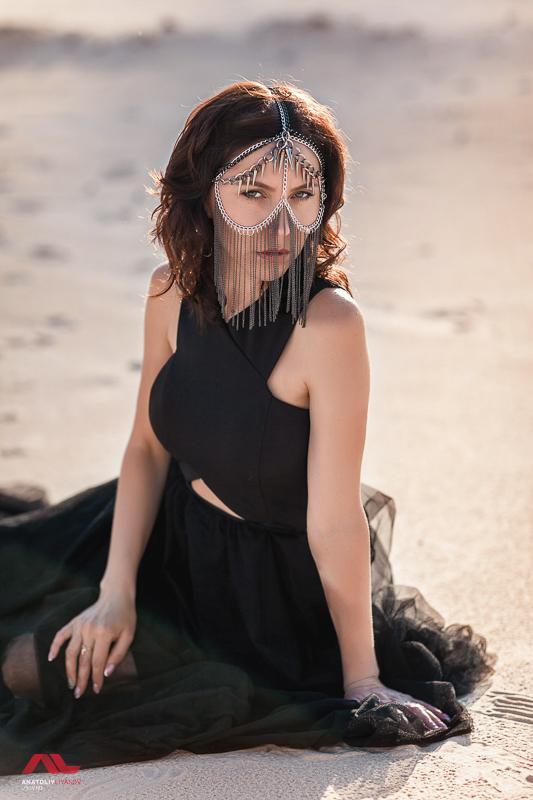 Фото в черном платье на фоне песка