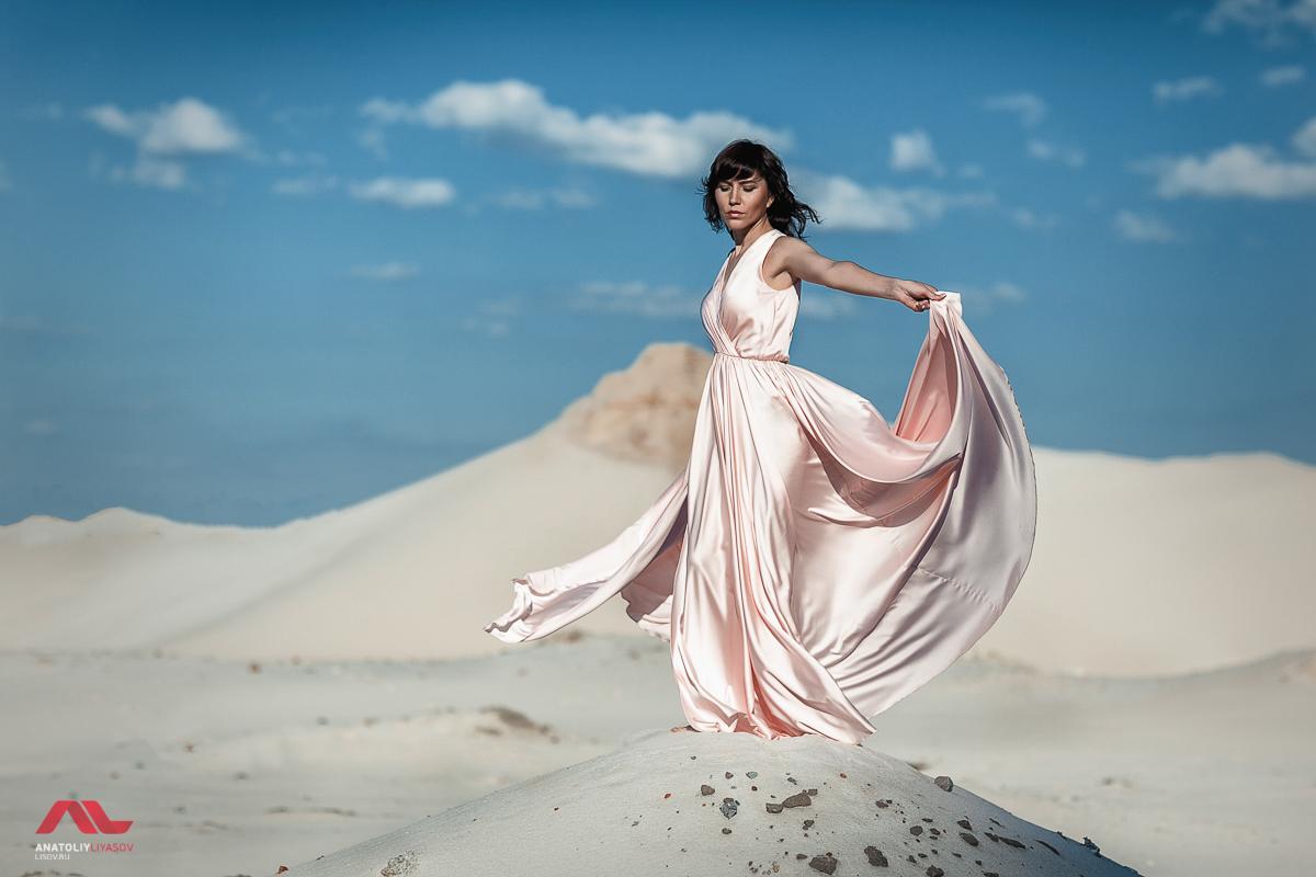 Девушка в розовом платье на фоне песка